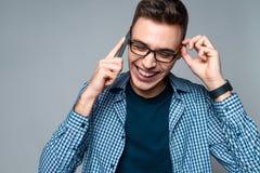 Молодые умные беседы парня по телефону, регулируя стекла стоковое фото