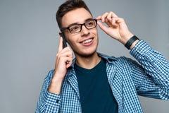 Молодые умные беседы парня по телефону, регулируя стекла стоковая фотография