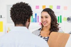 Молодые усмехаясь бизнесмены говоря друг к другу Стоковые Изображения
