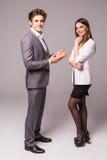 Молодые усмехаясь бизнес-леди и бизнесмен на серой предпосылке стоковые изображения rf