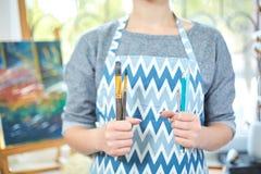 Молодые усмехаясь краски девушки на холсте с цветами масла в собственной мастерской окно на предпосылке белизна пятна краски маск Стоковые Изображения RF