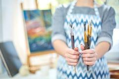 Молодые усмехаясь краски девушки на холсте с цветами масла в собственной мастерской окно на предпосылке белизна пятна краски маск Стоковое Фото