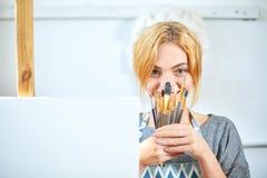 Молодые усмехаясь краски девушки на холсте с цветами масла в собственной мастерской окно на предпосылке белизна пятна краски маск Стоковая Фотография