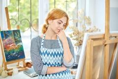 Молодые усмехаясь краски девушки на холсте с цветами масла в собственной мастерской окно на предпосылке белизна пятна краски маск стоковое изображение