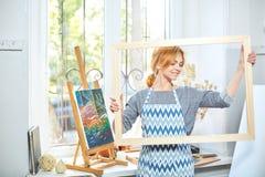 Молодые усмехаясь краски девушки на холсте с цветами масла в собственной мастерской окно на предпосылке белизна пятна краски маск Стоковое Изображение RF