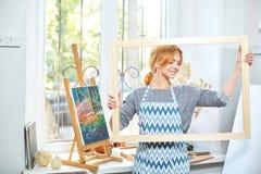 Молодые усмехаясь краски девушки на холсте с цветами масла в собственной мастерской окно на предпосылке белизна пятна краски маск Стоковое фото RF