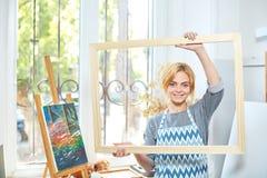 Молодые усмехаясь краски девушки на холсте с цветами масла в собственной мастерской окно на предпосылке белизна пятна краски маск Стоковые Фотографии RF