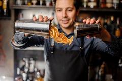 Молодые усмехаясь куски бармена лить свежего оранжевого плодоовощ стоковое фото