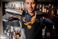 Молодые усмехаясь куски бармена лить свежего оранжевого плодоовощ стоковое изображение rf