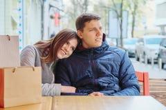 Молодые усмехаясь пары с хозяйственными сумками в кафе улицы, ждать чашке кофе и чае стоковое изображение rf