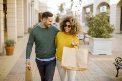 Молодые усмехаясь покупки пар в городской улице стоковое фото