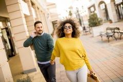 Молодые усмехаясь покупки пар в городской улице стоковые изображения rf