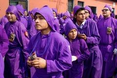 Молодые фиолетовые облачённые люди намекая на шествии Сан Bartolome de Becerra в 1a Avenida, Антигуе, Гватемале Стоковое Изображение RF