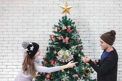 Молодые хорошие смотря пары Cacausian украшают toge рождественской елки стоковая фотография