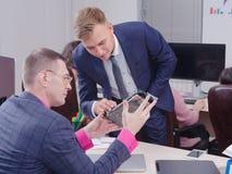 Молодые человеки в офисе смотрят видеокарту стоковая фотография