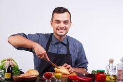 Молодые человеки делая горячую сосиску в кухне Ингридиенты для хот-дога стоковое изображение rf