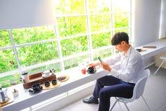 Молодые человеки едят кофе и принимают фотоснимок красивых рыб стоковые фотографии rf