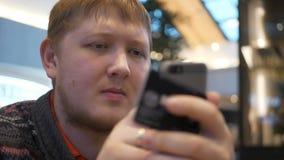 Молодые человеки используя smartphone кладя promo-код на фуд-корт в торговый центр Молодого человека оплаченное для онлайн покупо видеоматериал