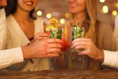 Молодые человеки и женщины выпивая коктеиль на партии Стоковая Фотография RF