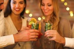 Молодые человеки и женщины выпивая коктеиль на партии Стоковое Фото