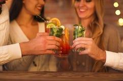Молодые человеки и женщины выпивая коктеиль на партии Стоковые Фотографии RF