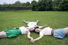 Молодые человеки и женщины лежа на траве Стоковое Изображение