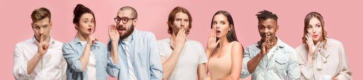 Молодые человеки и женщины шепча секрету за руками над розовой предпосылкой Стоковые Фото