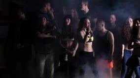Молодые человеки тазобедренной партии хмеля радостные и сексуальные девушки танцуя в темной комнате видеоматериал