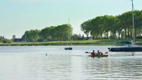 Молодые человеки canoeing в озере Стоковые Изображения
