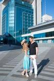 Молодые человек и женщина пар встречали в квадрате около бушеля высотного здания Стоковые Изображения RF