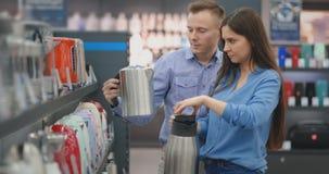 Молодые человек и женщина пар в магазине приборов выбирают электричес видеоматериал