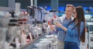 Молодые человек и женщина пар в магазине приборов выбирают blender для их кухни сток-видео