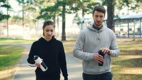 Молодые человек и женщина пар в sportswear идут в лес держа бутылки с водой, говорить, смеяться и выпивать сток-видео