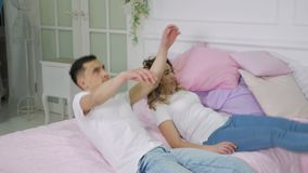 Молодые человек и женщина пар падают на кровать, замедленное движение сток-видео