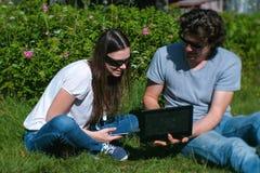 Молодые человек и женщина пар работают совместно на черни и компьтер-книжке сидя в парке стоковые фото