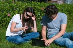 Молодые человек и женщина пар работают совместно на черни и компьтер-книжке сидя в парке стоковые изображения
