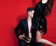 Молодые человек и женщина пар стиля моды на красной сексуальной предпосылке, Стоковые Изображения RF