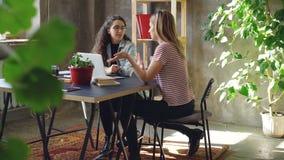Молодые enterpreneurs duscussing стратегия рекламы пока сидящ на таблице в современном офисе Женщины говорят и видеоматериал