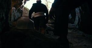 Молодые hikers в шлемах взбираясь вверх от темной пещеры сток-видео