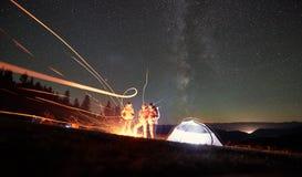 Друзья отдыхая около лагеря, лагерного костера под небом ночи звездным стоковое изображение