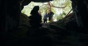 Молодые hikers друзей стоя на входе пещеры в лесе видеоматериал