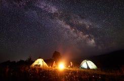 Молодые hikers пар отдыхая около загоренного шатра, располагаясь лагерем в горах на ноче под звёздным небом Стоковое Изображение