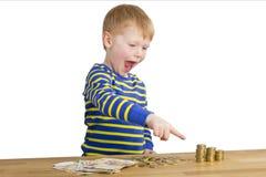 Молодые poits мальчика к башням денег Стоковое фото RF