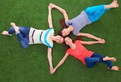 Молодые smilling женщины лежа на зеленой траве Стоковая Фотография