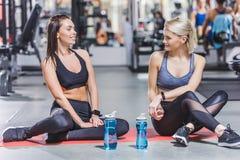 молодые sportive женщины ослабляя после тренировки на спортзале пока сидящ Стоковое фото RF