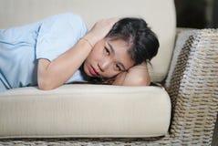 Молодым красивым грустным и подавленным азиатским китайским кризис тревожности кресла софы женщины дома сокрушанный чувством стра стоковая фотография