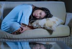 Молодым красивым грустным и подавленным азиатским японским кризис тревожности кресла софы женщины дома сокрушанный чувством страд стоковые фото