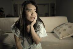 Молодым красивым грустным и подавленным азиатским японским кризис тревожности кресла софы женщины дома сокрушанный чувством страд стоковое изображение rf