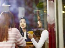 3 молодых азиатских женщины беседуя говорить в кофейне стоковое фото