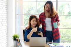 2 молодых азиатских женщины держа кофейную чашку пока работающ с подолом Стоковые Фотографии RF